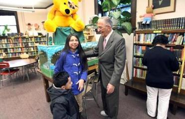 12-20-11: Chelsea, MA: 90 year old Morrie Seigal (cq), who is retiring from his position as an at large member of the Chelsea School Committee after 29 years is pictured as he talks to Sarai Hernandez (cq), age 12 and Darvin Lapop (cq), age 5 inside the Chelsea Public Library. (Globe Staff Photo/Jim Davis) section:nowk topic:01noseigal(1)